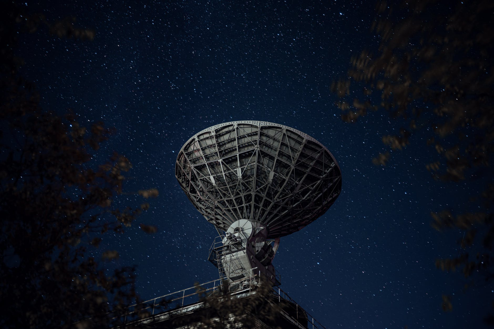 radio telescope against sky with stars