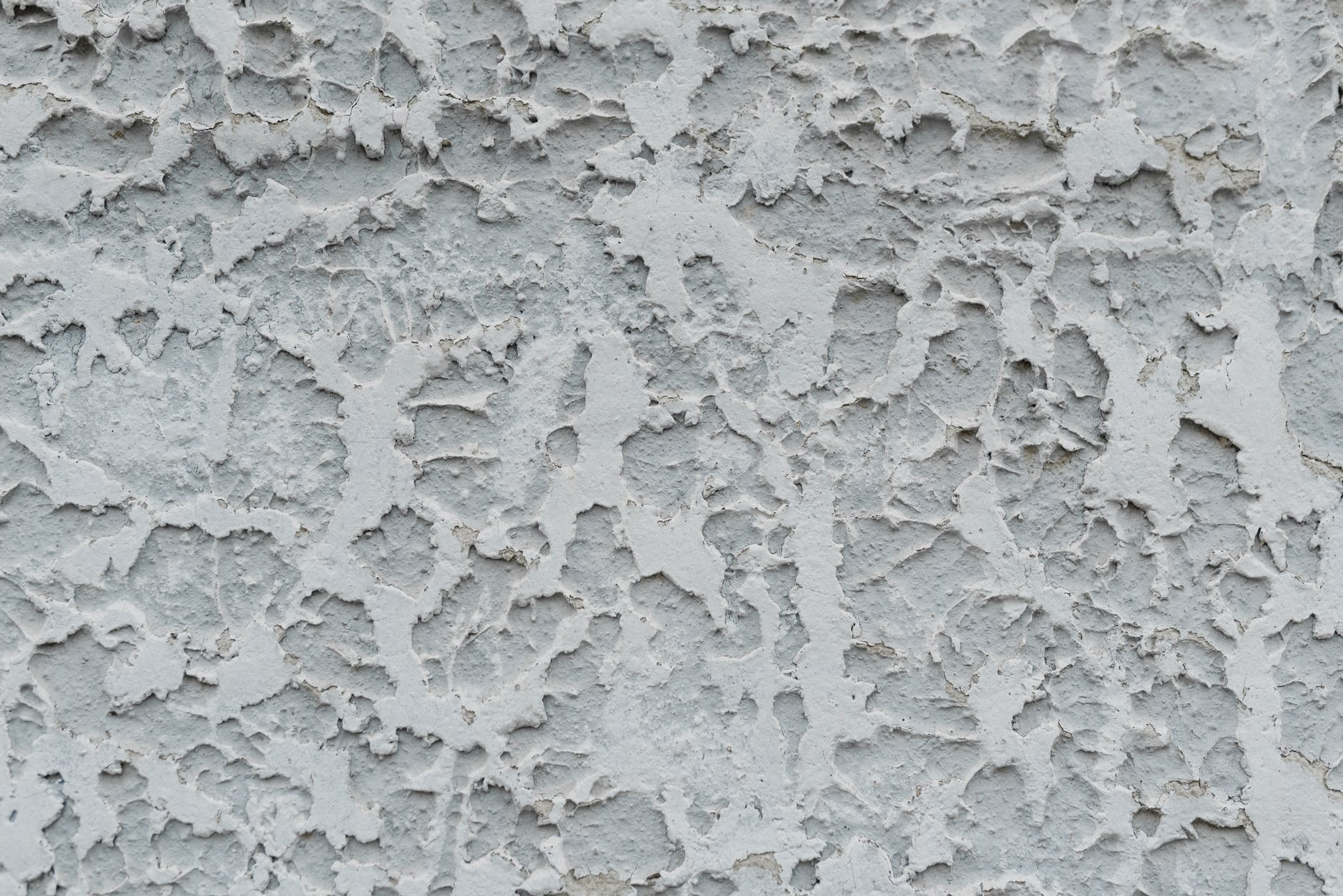 cracked gray stucco wall with cracked surface